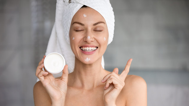 Funny attractive woman hold cream jar point at copy space