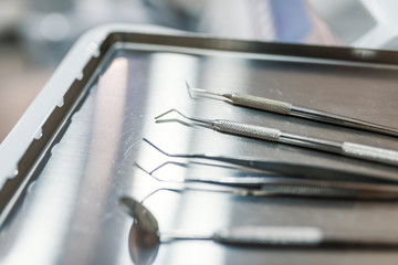 Professional Dentist tools in dental office: dentist mirror, forceps curved, explorer curved, dental explorer angular and explorer curved with chip, right. Dental Hygiene and Health conceptual image