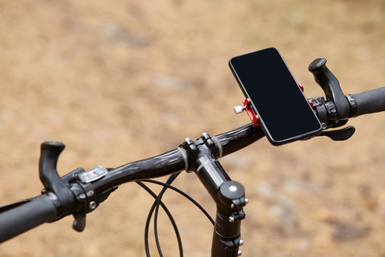 Black handlebar of sport bicycle over forest road background, having smartphone attached to right side, movement along road, gps navigator, going according to online map. Orientation concept.