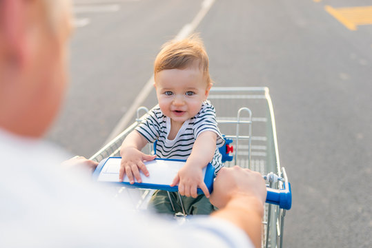 Boy sitting in the shopping cart at supermarket