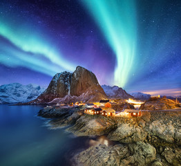 Aurora Borealis above Reine, Lofoten islands, Norway. Nothen light, mountains and houses. Winter landscape at the night time. Norway travel - image