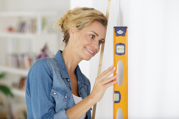 woman checking level of wall flatness