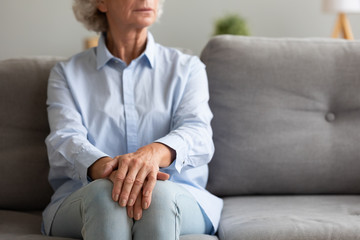 Fotomurales - Unhappy depressed senior woman sit alone on sofa, closeup view