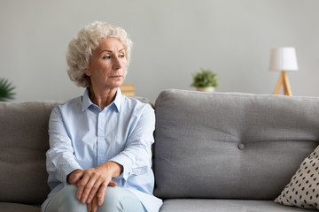Fotomurales - Pensive senior grandma looking away thinking of loneliness on couch