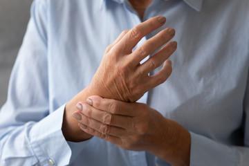 Senior lady massaging hand suffering from rheumatoid arthritis concept, closeup Fototapete