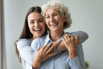 Cheerful affectionate two age generation women embracing indoors, family portrait