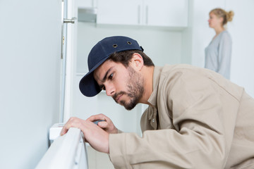 man fixing a heating radiator