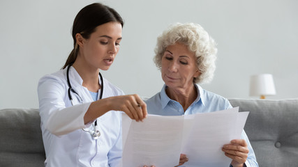 Fototapete - Serious young doctor explain insurance contract to elder grandma patient