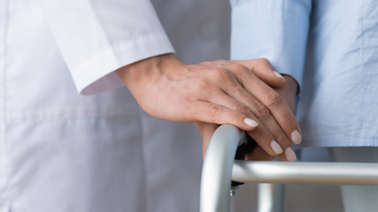 Fototapete - Female doctor holding senior patient hand using walking frame, closeup
