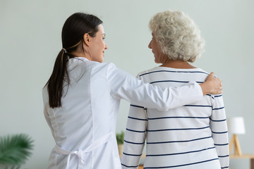 Fototapete - Young female physiotherapist help injured old grandma patient walking, physiotherapy