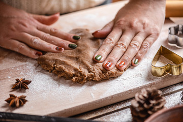Christmas family traditions. A woman uncovers a dough for making homemade gingerbread cookies. Close-up.