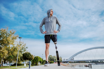 Fotomurales - Low angle view of sporty caucasian handicapped man in sportswear and with artificial leg standing with hands on hips on racetrack next to river and looking away.
