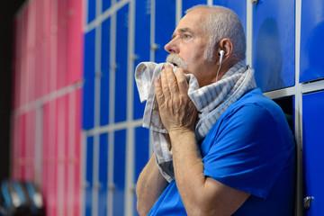 senior man wiping his sweat in the locker room