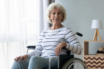 Fototapete - Happy disabled senior grandma sit on wheelchair looking at camera