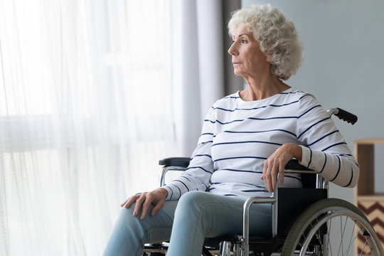 Sad paraplegic old woman sit on wheelchair look through window