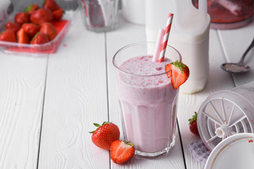 Strawberry protein shake on a white wooden background. Fresh milkshake with strawberries on a light table. A glass of strawberry smoothie.