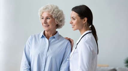 Fototapete - Happy old grandma and young woman nurse carer looking away