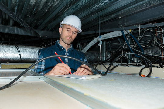 electrician making notes in roof space