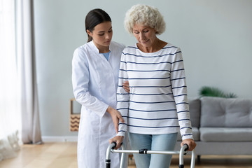 Fototapete - Young woman caregiver helping disabled old grandma patient using walker