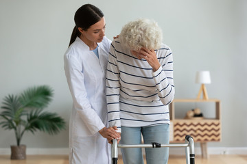 Fototapete - Young woman physiotherapist caregiver consoling sad injured old grandma patient