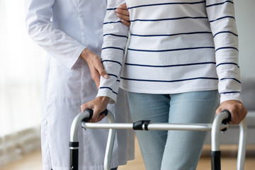 Fototapete - Female nurse helping old grandmother patient using walking frame, closeup