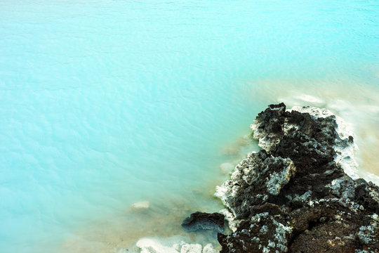 Volcanic rock in the famous blue lagoon in reykjavik/iceland. Blue green algae colors the water blue. Psoriasis and bathing concept. Copy space for text.