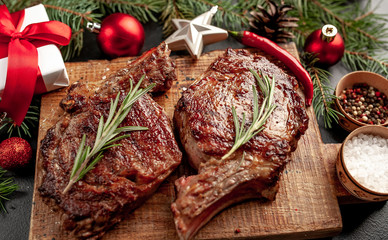 In de dag Steakhouse Christmas dinner for two, grilled beef steak ribeye, herbs and spices on a stone table with a Christmas tree and New Year's toys