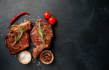 two grilled beef steaks with spices on a stone background with copy space