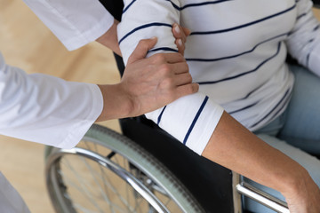 Fototapete - Helping hand of caretaker holding old woman on wheelchair, closeup