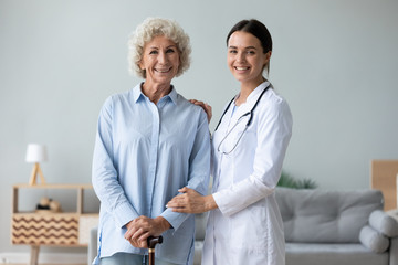 Fototapete - Female nurse helping old woman holding cane looking at camera