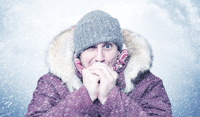 Frozen man in winter clothes warms his hands, cold, snow, frost, blizzard