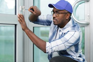 man working fittings on a window