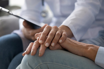 Young woman doctor holding hand of senior grandmother patient, closeup