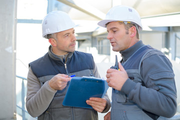 two workers at an industrial plant with a tablet