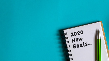 2020 new year goal, plan, action text on note pad. Top view or flat lay.