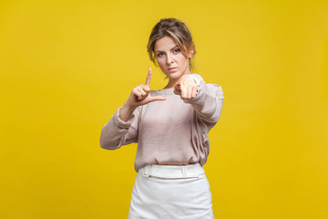 You are loser! Portrait of serious bossy woman with fair hair in casual blouse standing, showing loser gesture and pointing at camera with angry look. indoor studio shot isolated on yellow background