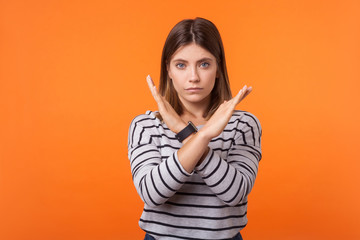 There is no way. Portrait of determined serious woman with brown hair in long sleeve striped shirt standing with crossed arms and gesturing no sign. indoor studio shot isolated on orange background