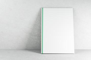Empty white book on concrete wallpaper