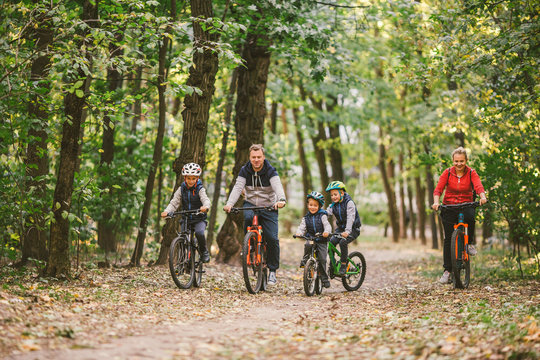parents and kids cycling on forest trail. Young family in warm clothes cycling in autumn park. Family mountain biking on forest. Theme family active sports outdoor recreation.