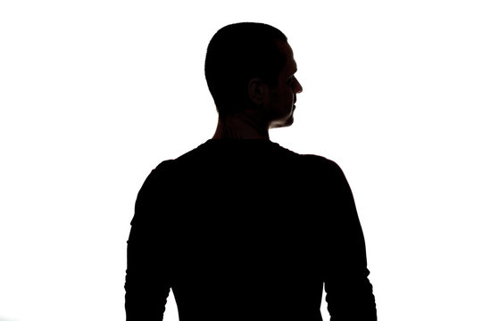 Silhouette of adult man standing back to camera in studio