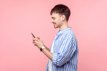 Side view of happy young brown-haired man with small beard in casual striped shirt holding phone, smiling while browsing social media, reading message. indoor studio shot isolated on pink background