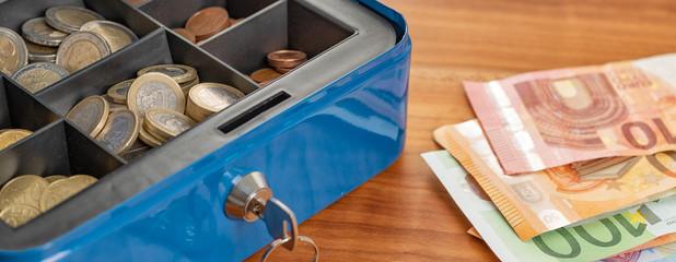 Fotomurales - Geldkassette mit Münzen und Scheinen