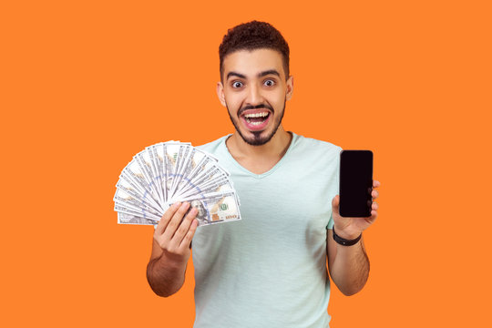 Online payment. Portrait of extremely happy man with beard in white t-shirt holding money and cellphone, looking with amazement, pleasantly surprised. indoor studio shot isolated on orange background