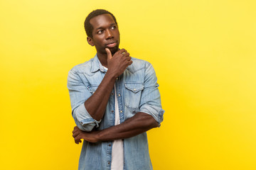 Thinking over decision. Portrait of pensive smart handsome man in denim casual shirt looking up, holding his chin while considering problem solution. indoor studio shot isolated on yellow background