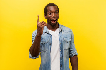 Portrait of creative inspired man in denim casual shirt pointing finger up, showing great idea sign, looking surprised by sudden solution, genius thoughts. studio shot isolated on yellow background
