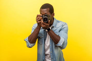 Portrait of male photographer or traveler in denim casual shirt holding professional digital dslr camera and focusing, taking photo, shooting video. indoor studio shot isolated on yellow background