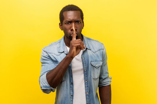Shh, keep silence. Portrait of serious handsome man in denim casual shirt with rolled up sleeves gesturing to be quiet, asking for secrecy conspiracy. indoor studio shot isolated on yellow background