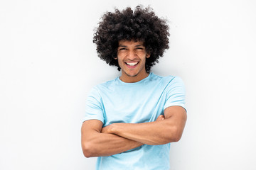 handsome young man with afro hair and arms crossed smiling by white background