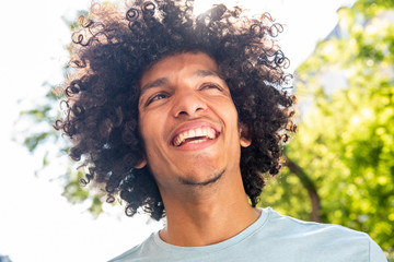 Close up handsome young North African man with afro hair smiling outside