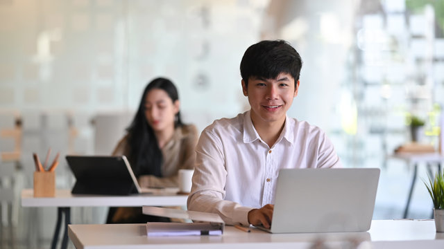 Asian man sitting on office workplace with laptop computer and looking at camera.